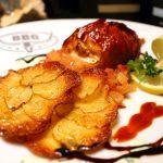 Fischpralinen im Baconmantel mit Garnelen und Käsefüllung, Parmesankartoffelblumen und einem Apfel-, Zwiebel-, Chilichutney